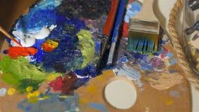 Pinsel taucht in die rote Farbe auf der Künstlerfarbpalette ein stock video footage