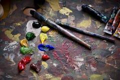 Pinsel und alte Ladeplatte des Malers Stockfotografie