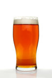 Pint of beer. With a frothy head against a white background stock photos