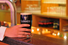 Pint of beer. Pint of guinness beer and man hand royalty free stock images