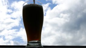 Pint of beer against blue sky - 4K stock footage