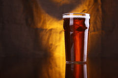 Pint of beer. Nonic pint glass with light beer with a warm colored drapery in the background royalty free stock photos