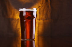 Pint of beer. Nonic pint glass with light beer with a warm colored drapery in the background stock image