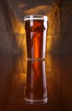 Pint of beer. Nonic pint glass with light beer with a warm colored drapery in the background Stock Photography