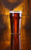 Pint of beer. Nonic pint glass with light beer with a warm colored drapery in the background stock images