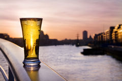 Pint of beer - over Dublin skyline. Pint of cold beer on the river Liffey, at sunset, over Dublin skyline stock images