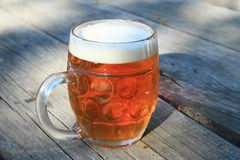 Pint of beer. With foam - cold beverage on wooden table royalty free stock images
