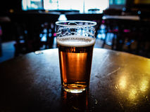 Pint of beer. Vintage looking pint of English bitter ale in a pub royalty free stock images