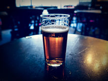 Pint of beer. Vintage looking pint of English bitter ale in a pub royalty free stock image