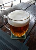 A pint of beer on a wooden table stock photography