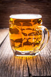 Pint of beer on a wooden table. Stock Images