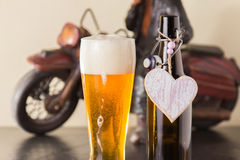 Chilled golden beer into a glass. Pint of chilled golden beer in a glass with a good frothy head alongside the empty beer bottle with a heart on it either Royalty Free Stock Photography