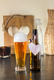 Pint of frothy beer with a heart. Pint of chilled golden beer in a glass with a good frothy head alongside the empty beer bottle with a heart on it either Royalty Free Stock Photos