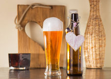 Pint of frothy beer with a heart. Pint of chilled golden beer in a glass with a good frothy head alongside the empty beer bottle with a heart on it either Stock Images