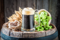 Pint of dark beer with wheat and hops on barrel. On wooden background stock photos