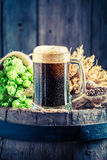 Pint of dark beer, wheat and hops on old barrel Stock Photos