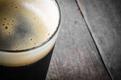 Pint of Dark Beer. On Wood Background stock photo