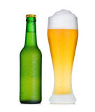 Pint glass of beer and bottle in dew Royalty Free Stock Image