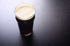 Pint glass of beer. Nonic pint glass of dark ale shot topdown over a dark background royalty free stock image