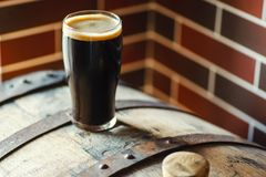 Pint of stout on a barrel. Pint glass of dark stout ale on a wooden barrel in a brewery Royalty Free Stock Photos