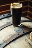 Pint of stout on a barrel. Pint glass of dark stout ale on a wooden barrel in a brewery Royalty Free Stock Photo