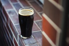Pint of stout on bricks. Pint glass of dark stout beer standing on a grunge brick windowsill Stock Images
