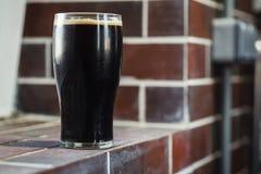 Pint of stout on bricks. Pint glass of dark stout beer standing on a grunge brick windowsill Stock Photo