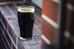 Pint of stout on bricks. Pint glass of dark stout beer standing on a grunge brick windowsill Stock Photos