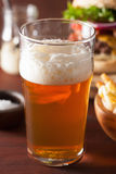 Pint glass of india pale ale beer and fastfood Royalty Free Stock Images