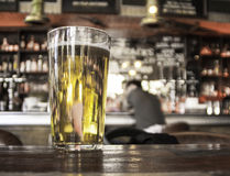Pint glass in a pub with a man in background. Glass of lager on a table in a pub in camden town, london, uk royalty free stock image
