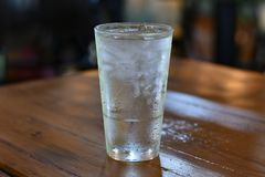 Condensation on Pint Glass Cool water. Pint glass of water on a restaurant wooden table royalty free stock photo