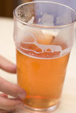 Pint Grasp. A Hand Reaches For A Pint Of Cider On A Pub Table Stock Image