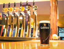 Pint of Guinness beer served in a pub. RIMINI, ITALY - OCTOBER 11, 2014: pint of beer served in a pub. Guinness is a world famous Irish dry stout created in the Royalty Free Stock Photo