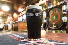 A pint of Guinness. A pint of Irish dry stout Guinness over the counter of The House of McDonnell, a traditional pub in Ballycastle, County Antrim, Northern royalty free stock photography