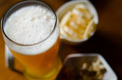Pint of lager beer in a glass, set of various snacks, a standard. Set of drinking and eating in a pub, beer and snacks Royalty Free Stock Photo
