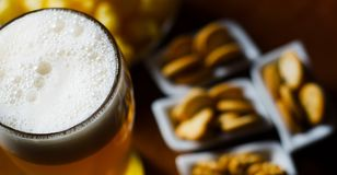 Pint of lager beer in a glass, set of various snacks, a standard. Set of drinking and eating in a pub, beer and snacks Stock Photo