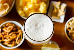 Pint of lager beer in a glass, set of various snacks, a standard. Set of drinking and eating in a pub, beer and snacks royalty free stock images