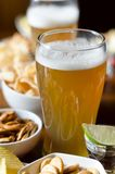 Pint of lager beer in a glass, set of various snacks, a standard. Set of drinking and eating in a pub, beer and snacks stock photography
