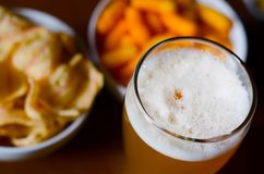 Pint of lager beer in a glass, set of various snacks, a standard. Set of drinking and eating in a pub, beer and snacks Stock Images