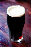 Pint of Stout. Chilled Pint of Stout in a pub setting Royalty Free Stock Photos