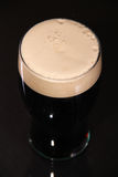 Pint of stout. A pint of irish stout for St. patrick day on a dark background Stock Images