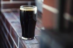 Pint of stout on bricks. Pint glass of dark stout beer standing on a grunge brick windowsill Royalty Free Stock Photos