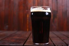 Pint of stout. A pint glass full of dark stout ale standing ona wooden table Stock Photos