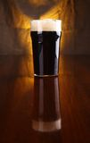 Pint of stout. Nonic pint of dark stout beer on a table with a warm colored drapery in the background Royalty Free Stock Photo