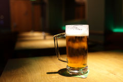 Pint on a table. Pint on a wooden table at a pub royalty free stock image
