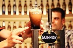 Pint van Guiness op de teller bij Guiness-Pakhuisbrouwerij met vinger het richten en persoon bij de achtergrond Stock Afbeeldingen