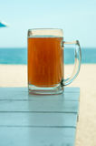 Pint  on wooden table and the sea Royalty Free Stock Photo