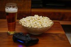 Pinta da bacia da cerveja de pipoca e de gamepad no home entertainment de madeira do fundo fotos de stock royalty free