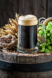 Pinta da cerveja escura com os ingredientes no tambor velho fotos de stock