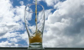Pinta de cerveza contra el cielo azul Imagen de archivo